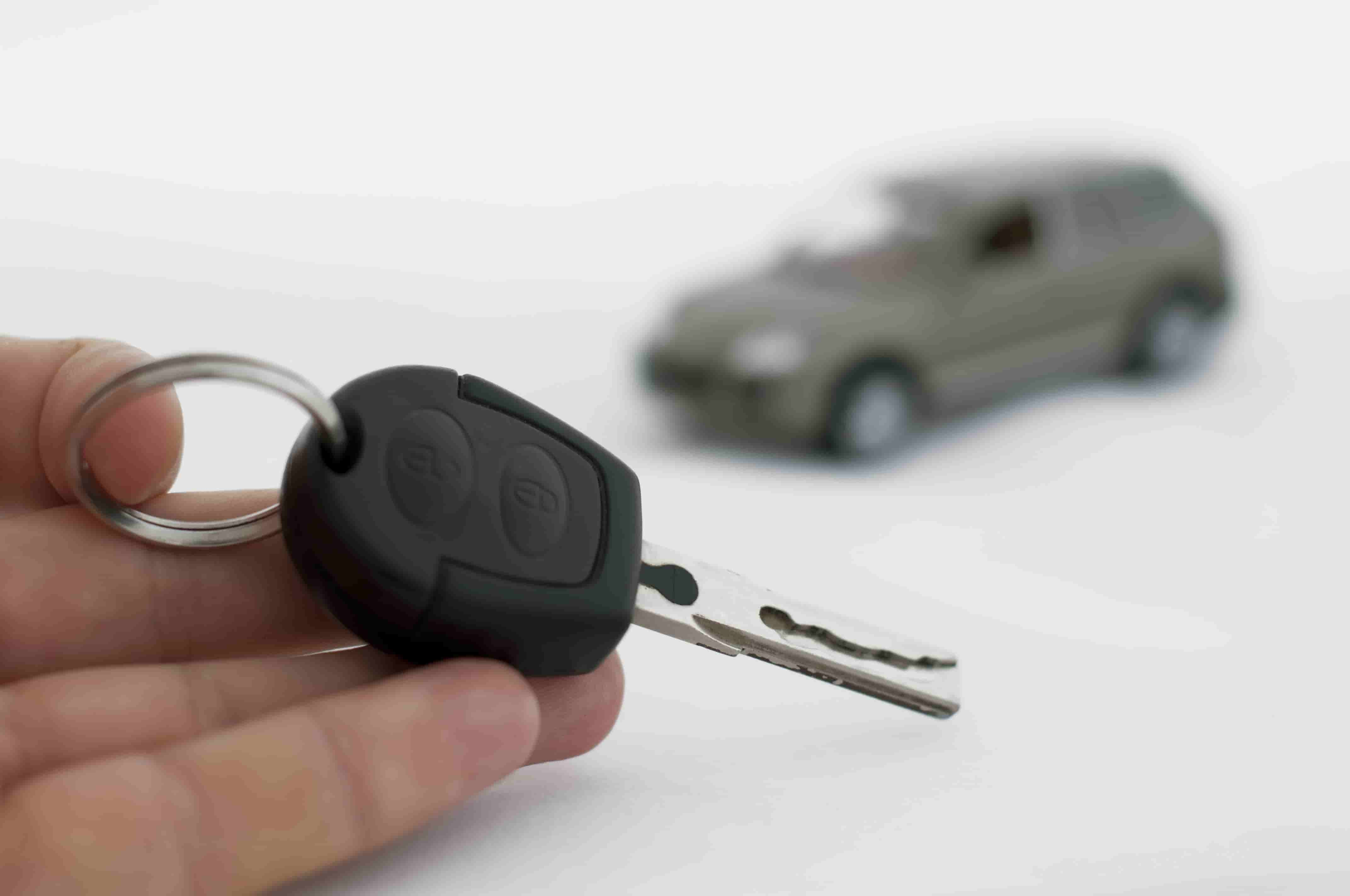 Hand holding keys and a car in the background